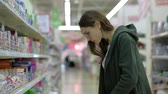 Female shopping in a large supermarket, selects hygienic products from the storefront. Slowmotion. Vídeos