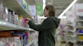 Attractive girl with glasses shopping in a large supermarket, selects hygienic products from the storefront. Slowmotion.