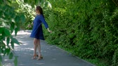handbag : A young woman in a blue dress and sunglasses walking in the city Park. Lady dancing in the street with a peony flower. Stock Footage