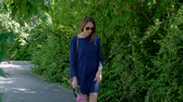 сцепление : A young woman in a blue dress and sunglasses walking in the city Park. Lady walking down the alley with a pink peony flower Стоковые видеозаписи