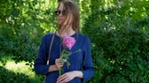 Portrait of a girl in sunglasses. Expectation. A young woman stands in a summer Park with a flower. Vídeos