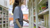 Woman in the store shopping with a grocery basket. Young women chooses cooking utensils. Vídeos