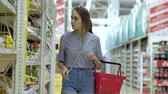 agd : Woman in the store shopping with a grocery basket. Young women chooses cooking utensils. Wideo