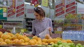 A young woman buys oranges. Veganism, Vegetarianism, Fructarians, the Woman in the supermarket. Vídeos
