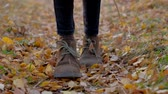 striding : close up - tourists legs walking on the background of fallen, rustling autumn leaves on forest road