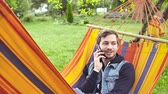 relaxation : 4k Hipster young man talking on the mobile phone in a hammock. Calling friends concept Stock Footage