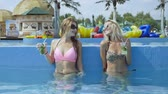 não alcoólica : Two beautiful sexy girlfriends talking and drink cocktails in a swiming pool