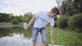 voluntário : Young man volunteer pulls a plastic bottle from a pond and throw in garbage bag
