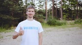 voluntário : Confident young man in volunteer t-shirt showing thumb up and looking at camera