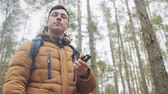 oryantasyon : Young man explorer searching direction with compass in winter forest Stok Video