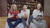 controlador : Group of three funny teen friends playing video games at home