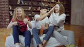 дающий : Three happy friends playing video games and giving high five