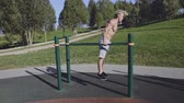 párhuzamos : Young fit man doing triceps dips on parallel bars on sports playground Stock mozgókép