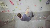 skalní útes : Free climber young man on artificial climbing wall rock in bouldering gym Dostupné videozáznamy