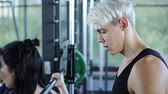 поднимать : Young girl doing exercises with barbell in gym with personal trainer