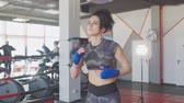Brunette female boxer at training inside a boxing ring, slow motion