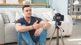 Young male blogger talking on digital camera recording video vlog at home