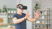 Man wearing virtual reality goggles. Handsome male using VR headset at home