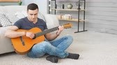compor : Young man playing acoustic guitar while sitting on carpet in living room