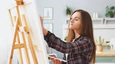 cavalete : A young woman painter draws a picture on canvas on an easel at home