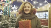 milagre : Portrait of young happy smiling girl posing with gift box at Christmas fair.