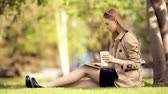 A smiling young woman with a tablet pc and a coffee cup sitting on the green grass in a summer park. Vídeos