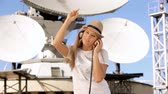 Happy young woman in hat listening to the music in vintage music headphones and dancing against background of satellite dish that receives wireless signals from satellites.