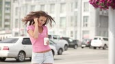 бить : Happy young woman with music headphones, holding a take away coffee cup, bobbing her head to the beat of the music and dancing against city traffic background.
