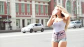 одноразовый : Happy young woman with music headphones, drinking take away coffee, dancing and singing her favorite songs against urban traffic background.