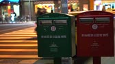 schránky : Taiwan postal street boxes. Red and green post next to street at night