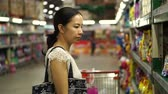 agd : Asian girl selects items in hypermarket, supermarket shelves Wideo
