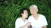 sentido : Asian senior couple whisper secret, sense of humour with green background Vídeos