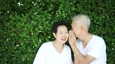 sentido : Asian senior couple whisper secret, sense of humour with green background Stock Footage