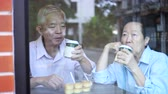 wealthy : Happy Asian elderly senior couple drinking morning coffee through cafe glass front Stock Footage