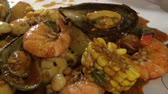 skrček : Seafood bucket boil in new orleans spice sauce eating with hand 4k