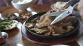 server : Scissors Cutting Korean Grilled Pork Ribs Service In Restaurant