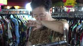 vendor : Asian Senior Woman Selling Clothes At Night Flea Market Stock Footage