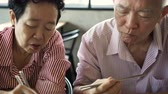 família : Asian senior couple eating Korean food using chopsticks
