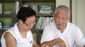Asian senior couple learning together in education center library