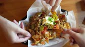 Hands enjoy eating Mexican nacho beef with cheese and cream Stok Video