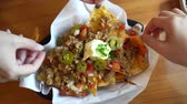 çili : Hands enjoy eating Mexican nacho beef with cheese and cream Stok Video
