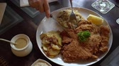 Eating pork Schnitzel Austria cuisine battered meat with  Sauerkraut and potatoes Stok Video