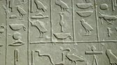 Close up of Egyptian hieroglyphics letters on wall at ancient architecture