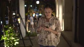 Asian woman chatting over smart phone at night outside on street