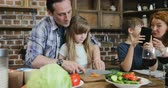 recipe : Family Together In Kitchen Father Helping Daughter To Cut Vegetables While Son And Mother Use Cell Smart Phone Talking Parents With Two Kids Preparing Food At Home Slow Motion 60