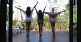 friends : Three Girls Stretching On Terrace In Morning Back Rear View, Looking At Tropical Garden, Slow Motion 60