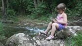 playful : little girl sitting next to a stream and play with tablet