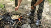 teljesen : Man frying fish on the fire. Frying freshwater fish. Grayling. Fish roasted in a frying pan on the fire.