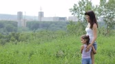 indicação : The girl with the kid on the mountain looking at the view of the city. Girl looking forward to the horizon. show a hand in the direction of the city. Family values Stock Footage