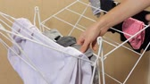 Male hands remove dry clothes from the dryer. A man does household chores
